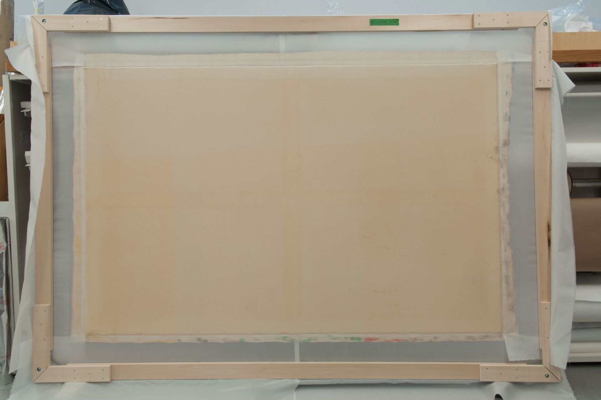 After releasing the canvas from its stretcher, bands of polyester fabric were adhered to the flattened tacking margins of the painting, allowing it to be secured to a temporary loom.