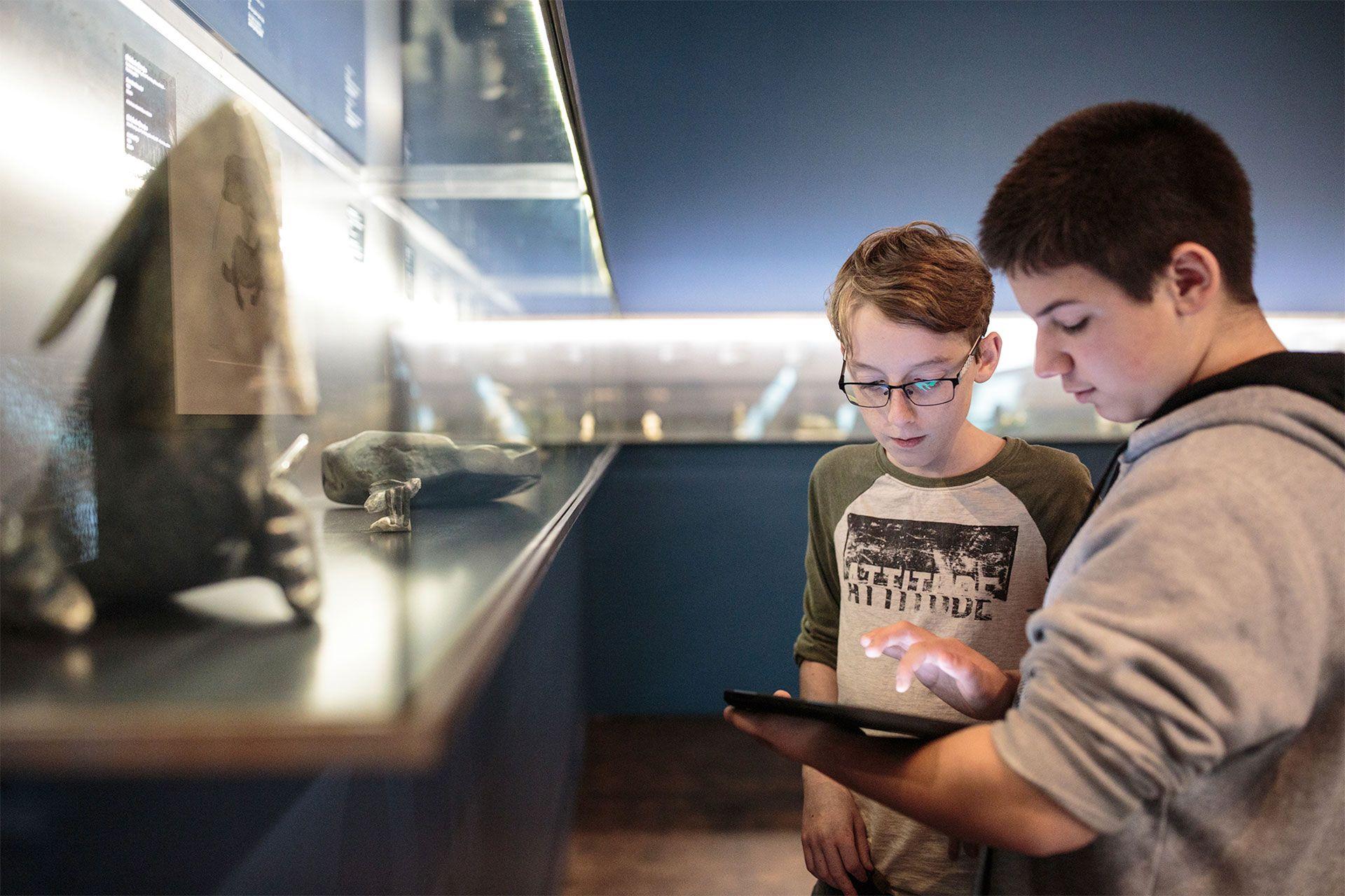 Photo de jeunes qui utilisent l'application Quelle Histoire dans une salle du musée.