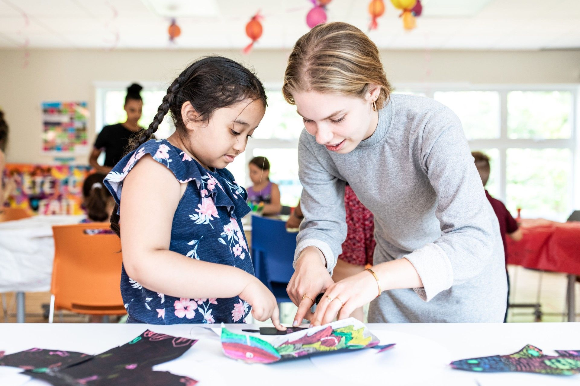 Girl doing crafts accompanied by a mediator