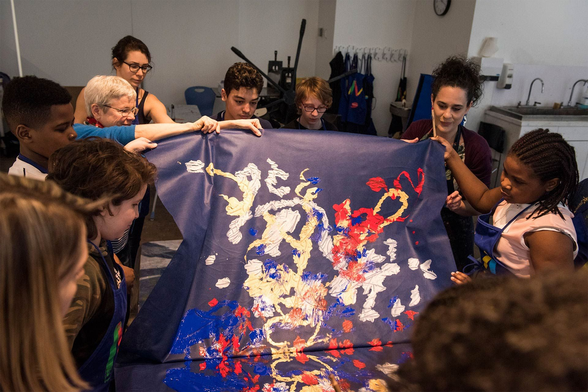 A group of children are doing a painting on a large canvas. Photo Caroline Hayeur (Collectifs stock photo)