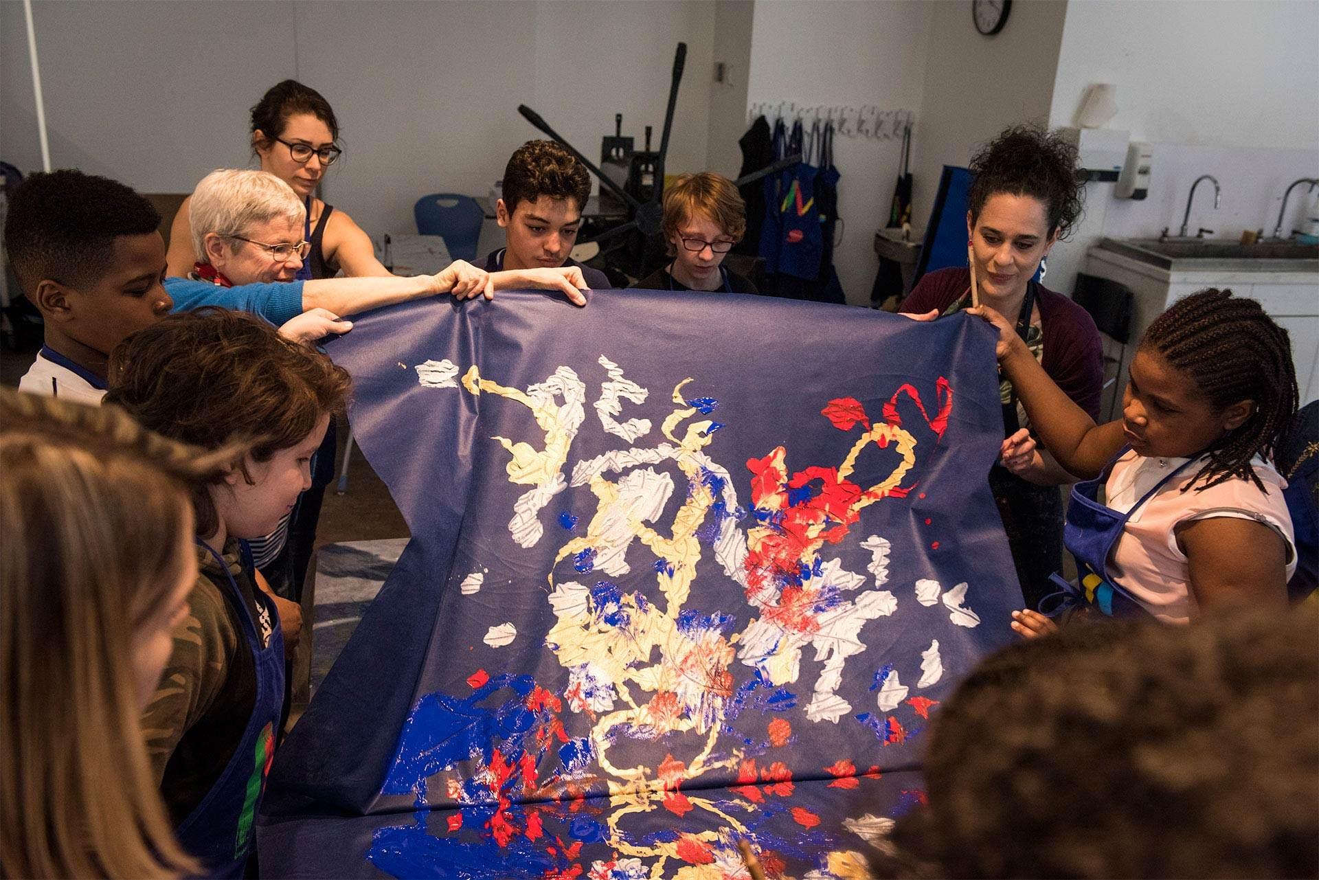 Un groupe de jeunes fait une peinture sur une grande toile. Photo Caroline Hayeur (Collectifs stock photo)