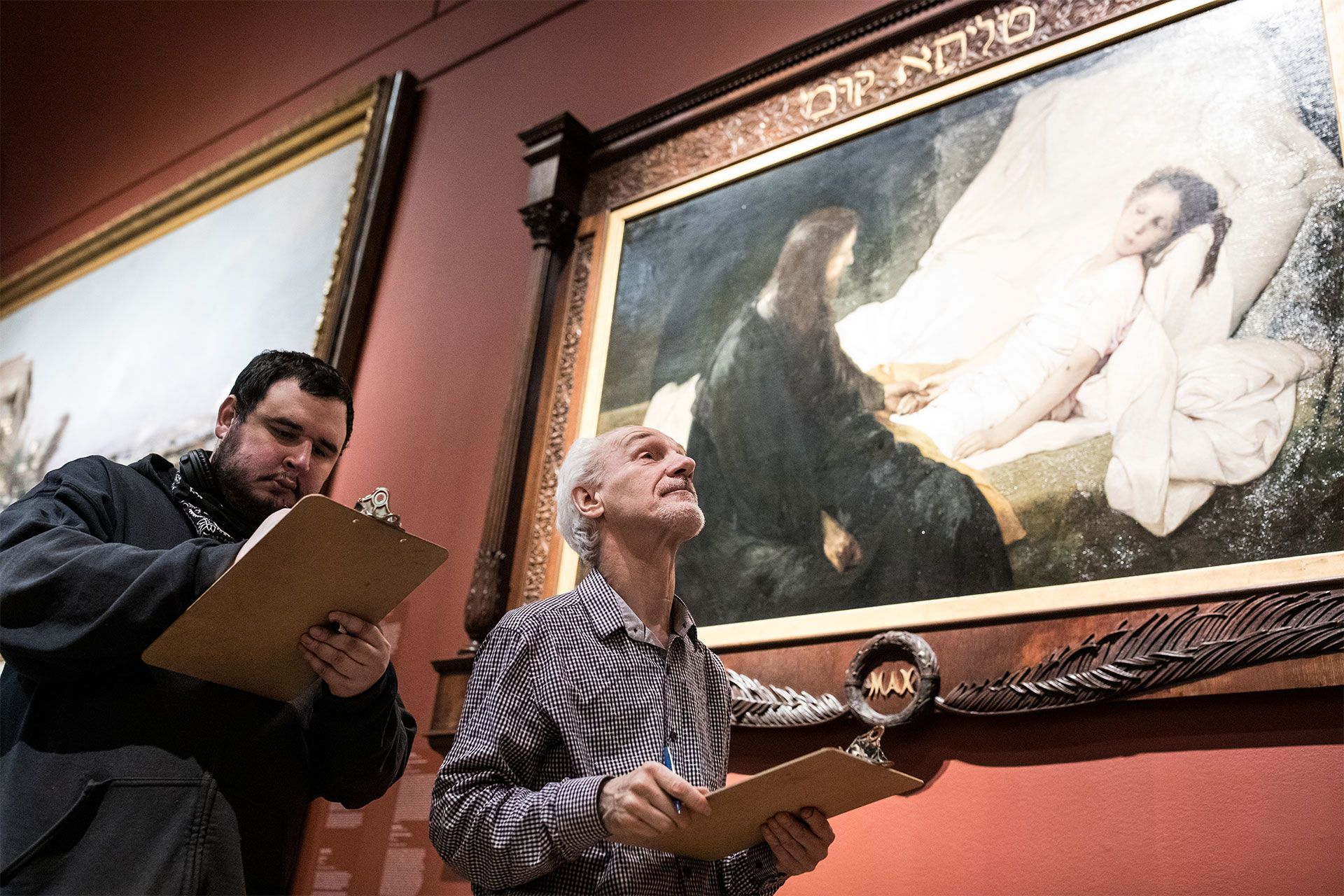 Two adults take notes during a tour of a Museum collection.