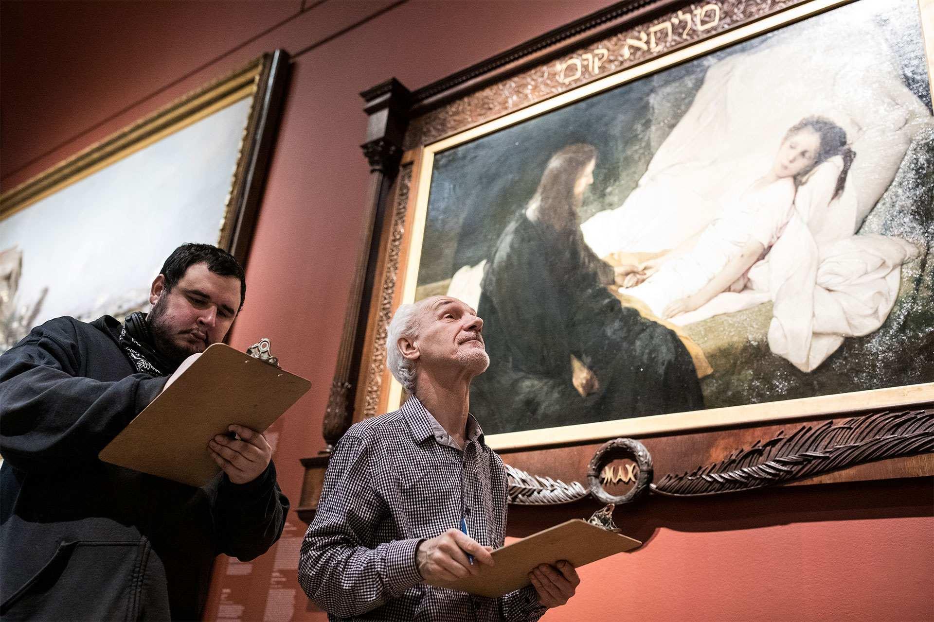 Deux adultes prennent des notes pendant une visite d'une collection du Musée.