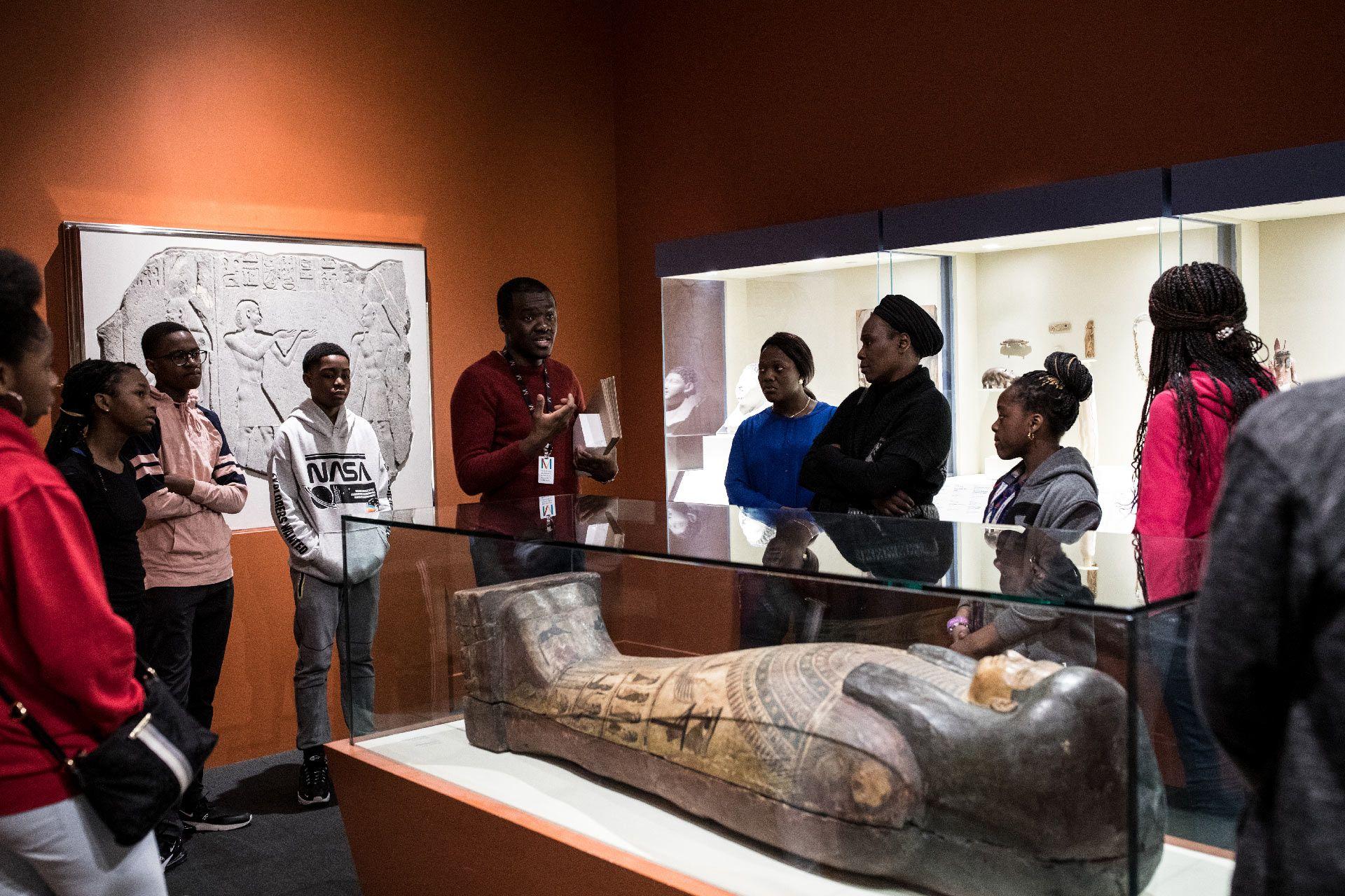 enfants et adultes devant un sarcophage de l'exposition Momies égyptiennes : Passé retrouvé, mystères dévoilés du MBAM