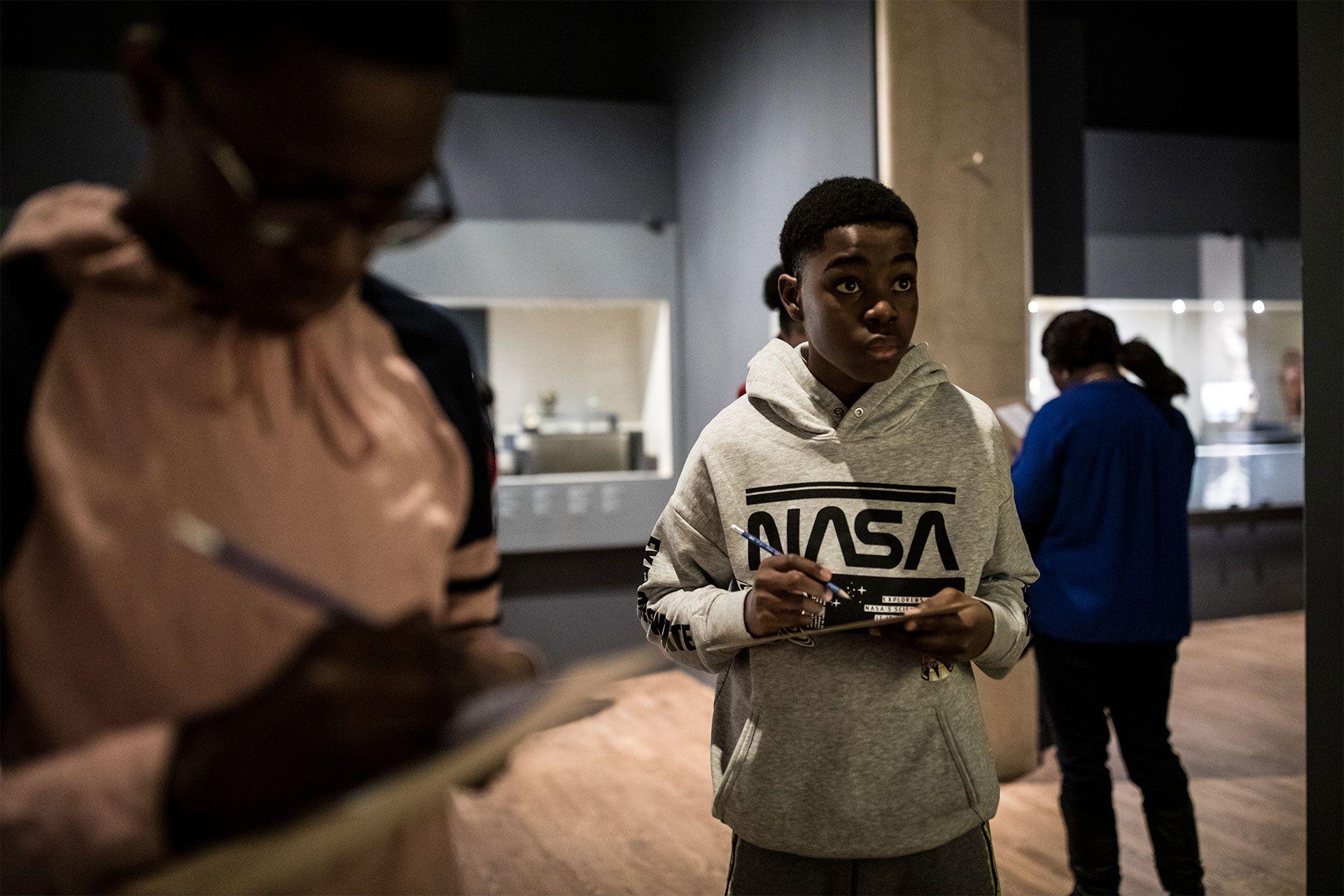 Un élève prends des notes en visitant une collection du Musée.