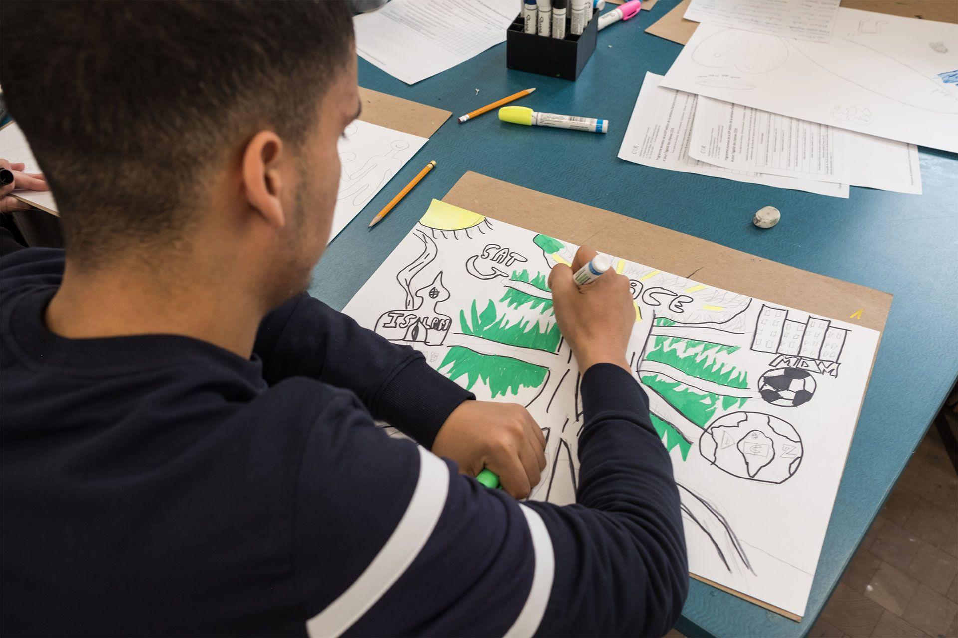 A teenager draws.