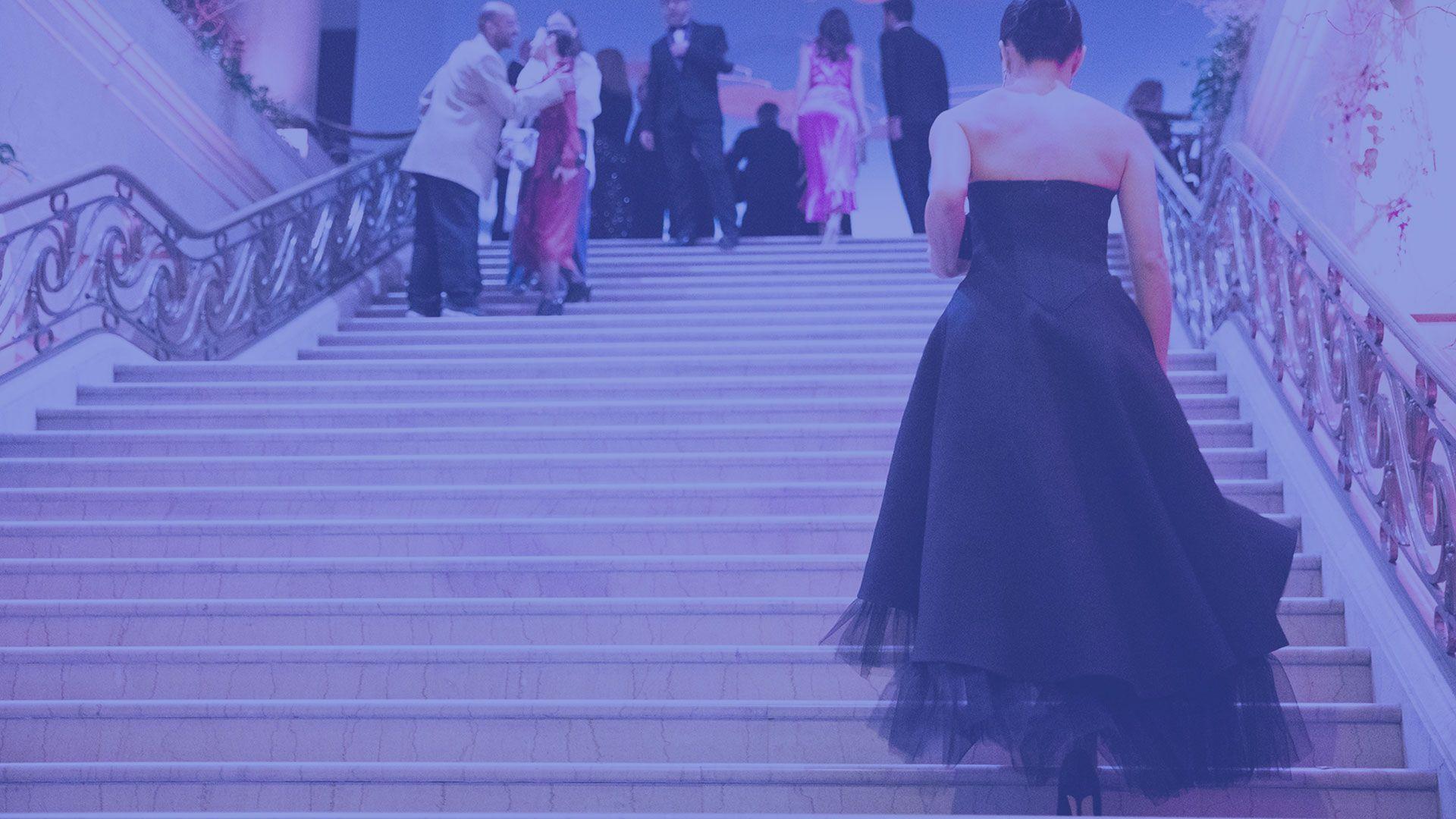 Une femme en robe de soirée monte les marches d'un escalier.