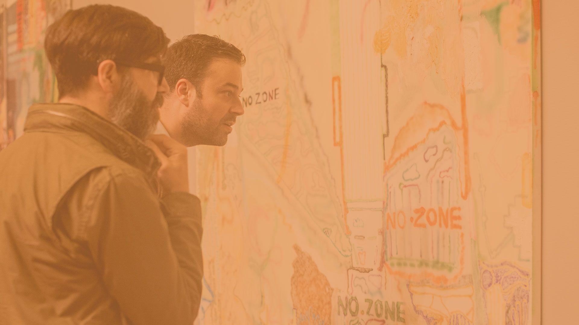 Deux hommes regardent un tableau lors d'une exposition.