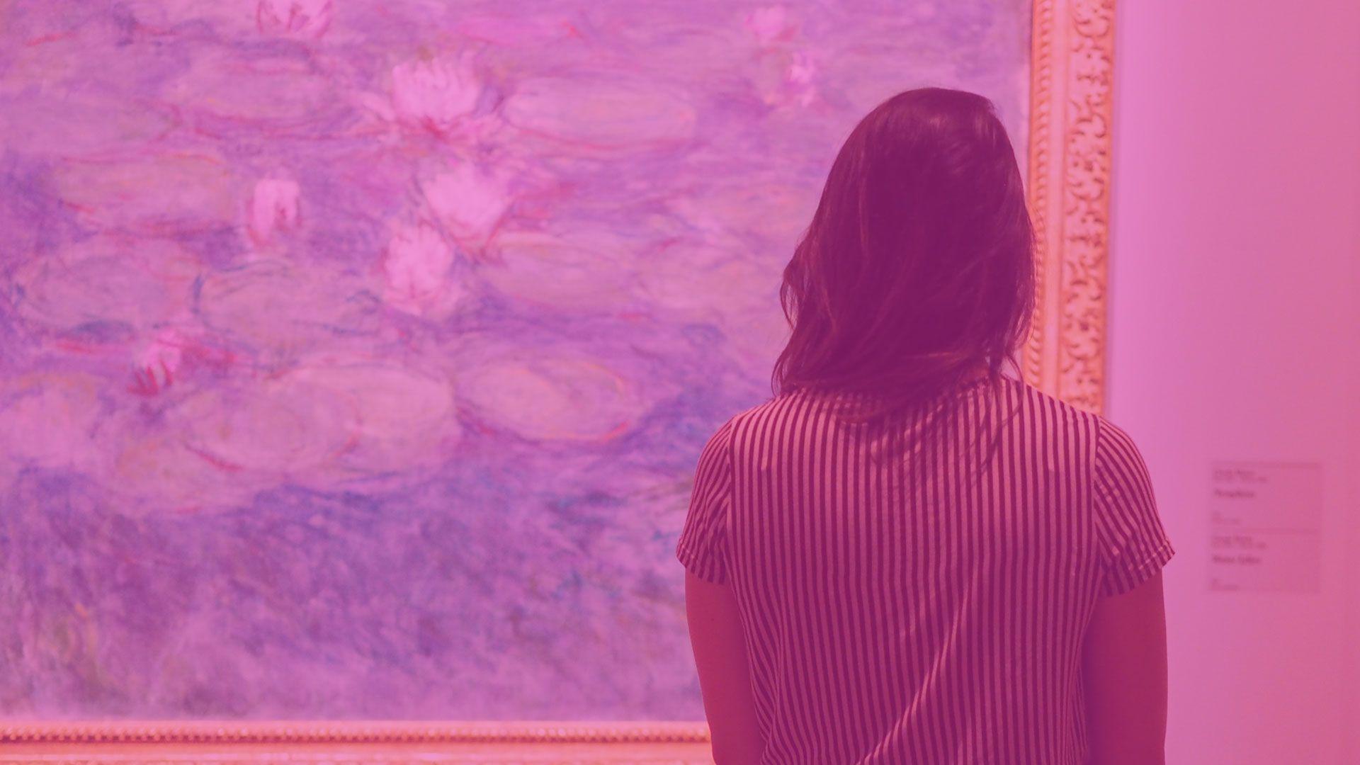 Une femme regarde un tableau de l'exposition Signac : Paris au temps du post impressionisme.