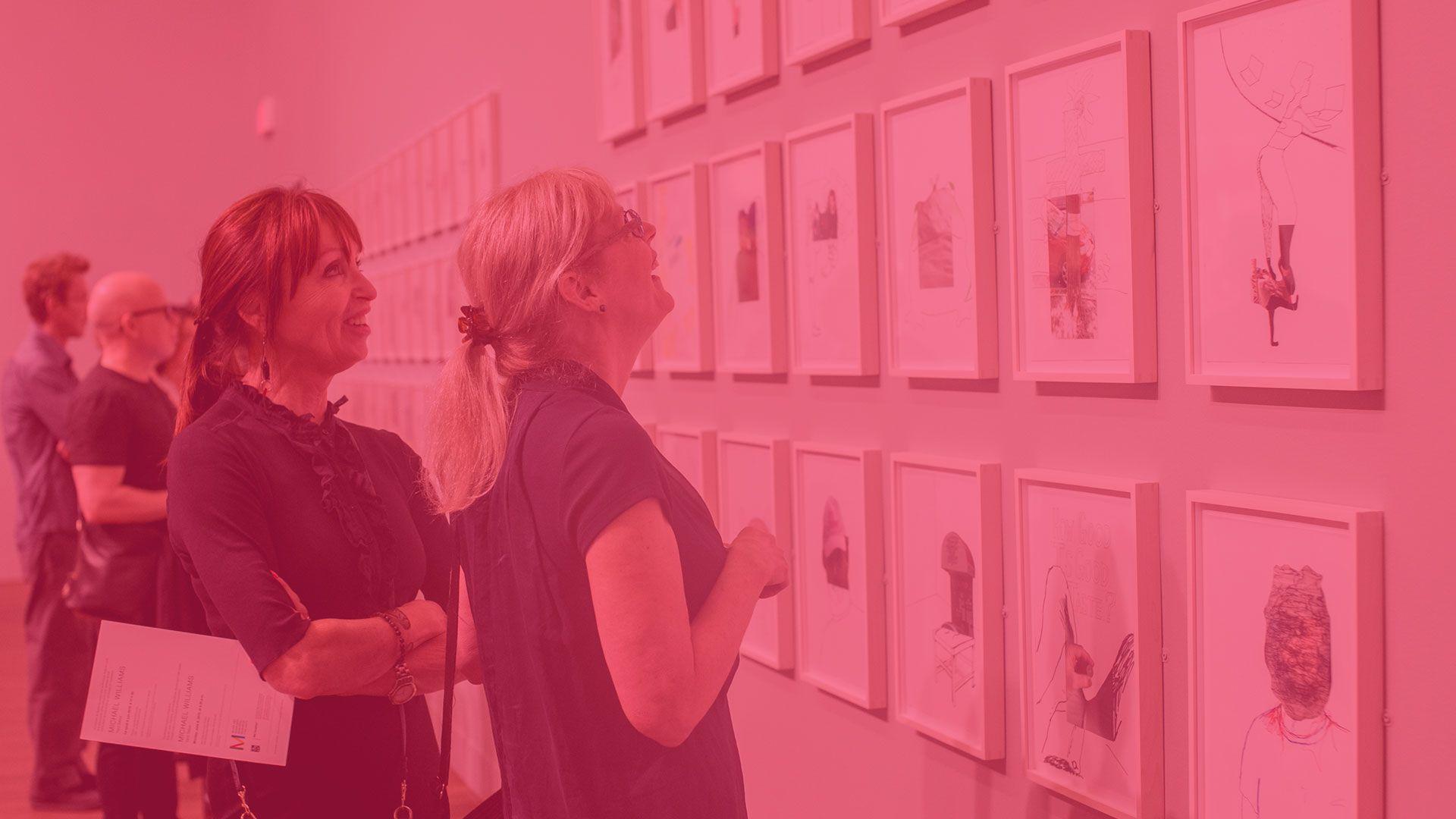 Deux femmes regardent un tableau lors d'une exposition.