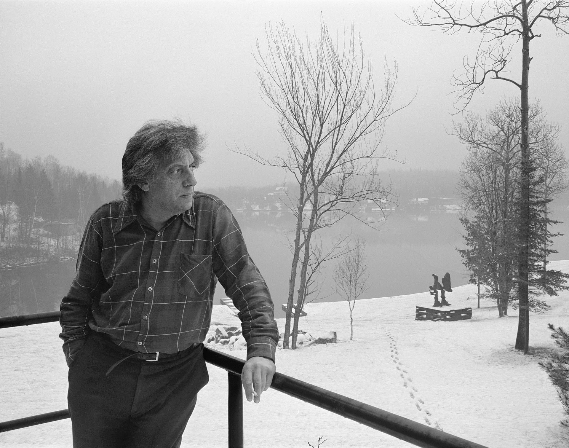 "Basil Zarov (1905 (?)-1998), Jean Paul Riopelle outside of the Studio at Sainte-Marguerite-du-Lac-Masson with ""La Défaite"" in the Distance, about 1976, black and white photograph. Library and Archives Canada, Ottawa. © Estate of Jean Paul Riopelle / SOCAN (2020). Photo © Library and Archives Canada. Reproduced with the permission of Library and Archives Canada/Basil Zarov fonds/e011205146"